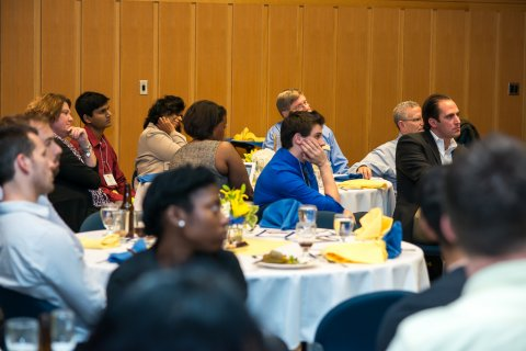 Alumni sitting at tables during event