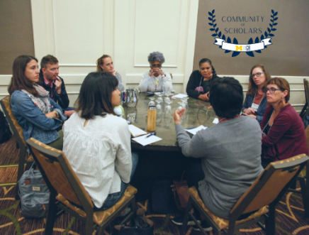 Community of Scholars logo featured on a photo with participants in dialogue sitting at a round table.
